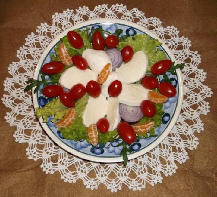 Ser mozzarella w plastrach z sałatą, pomidorkami koktajlowymi, rukolą i mandarynkami
