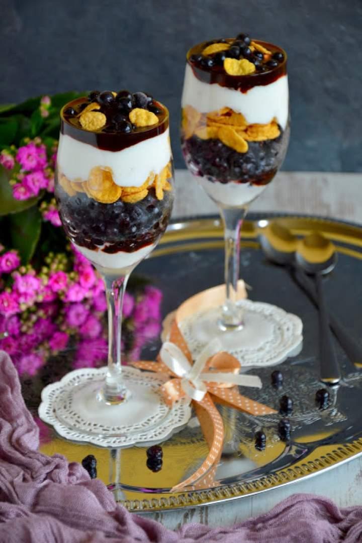 Śniadaniowy pucharek jagodowy z płatkami i jogurtem