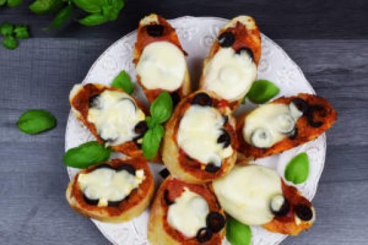 Zapiekana bagietka zmozzarellą, pesto, oliwkami, pomidorami