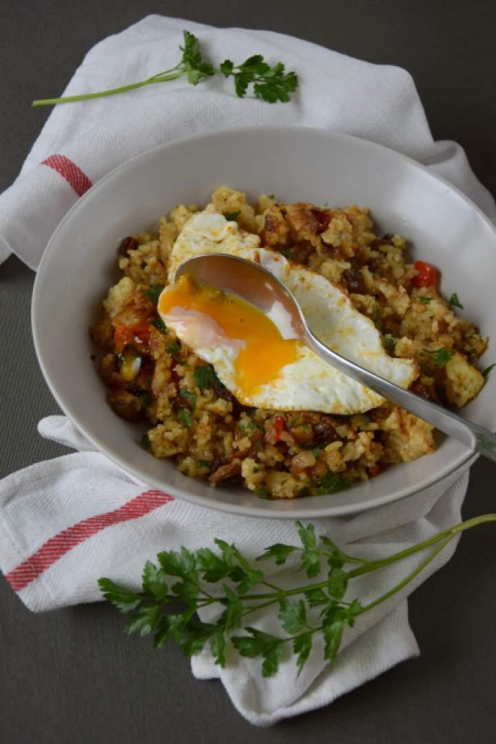 Ryż smażony z papryką i rodzynkami podany z jajkiem sadzonym