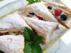 Ciasteczka z ciasta francuskiego z kremem i owocami.